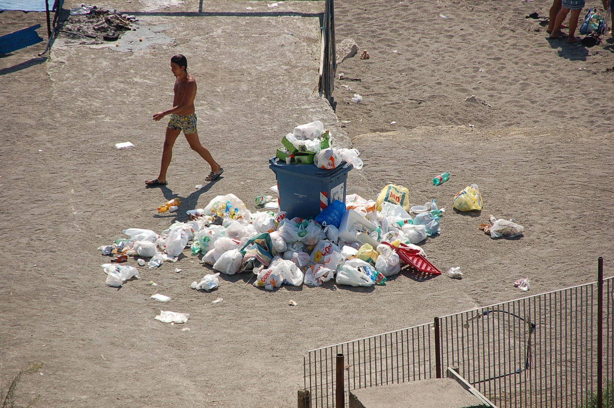 A young man walks past rubbish, which has piled up by a bin in Napoli, Italy. [Ra Boe/Wikipedia. 2010].