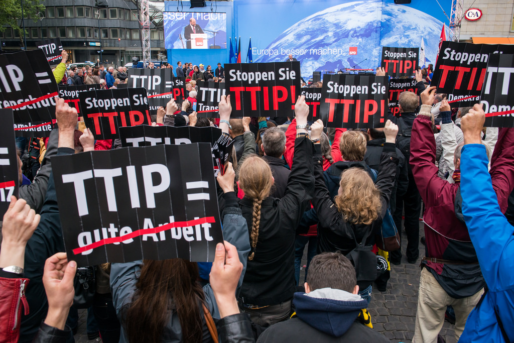 TTIP protestors hold up signs during a flashmob during a visit from Martin Schulz in the German city of Dortmund. May 2014 [campact/Flickr]