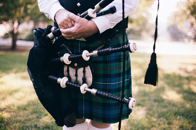 A man wearing and a kilt and holding bag pipes. [PublicDomainArchive/Pixabay].