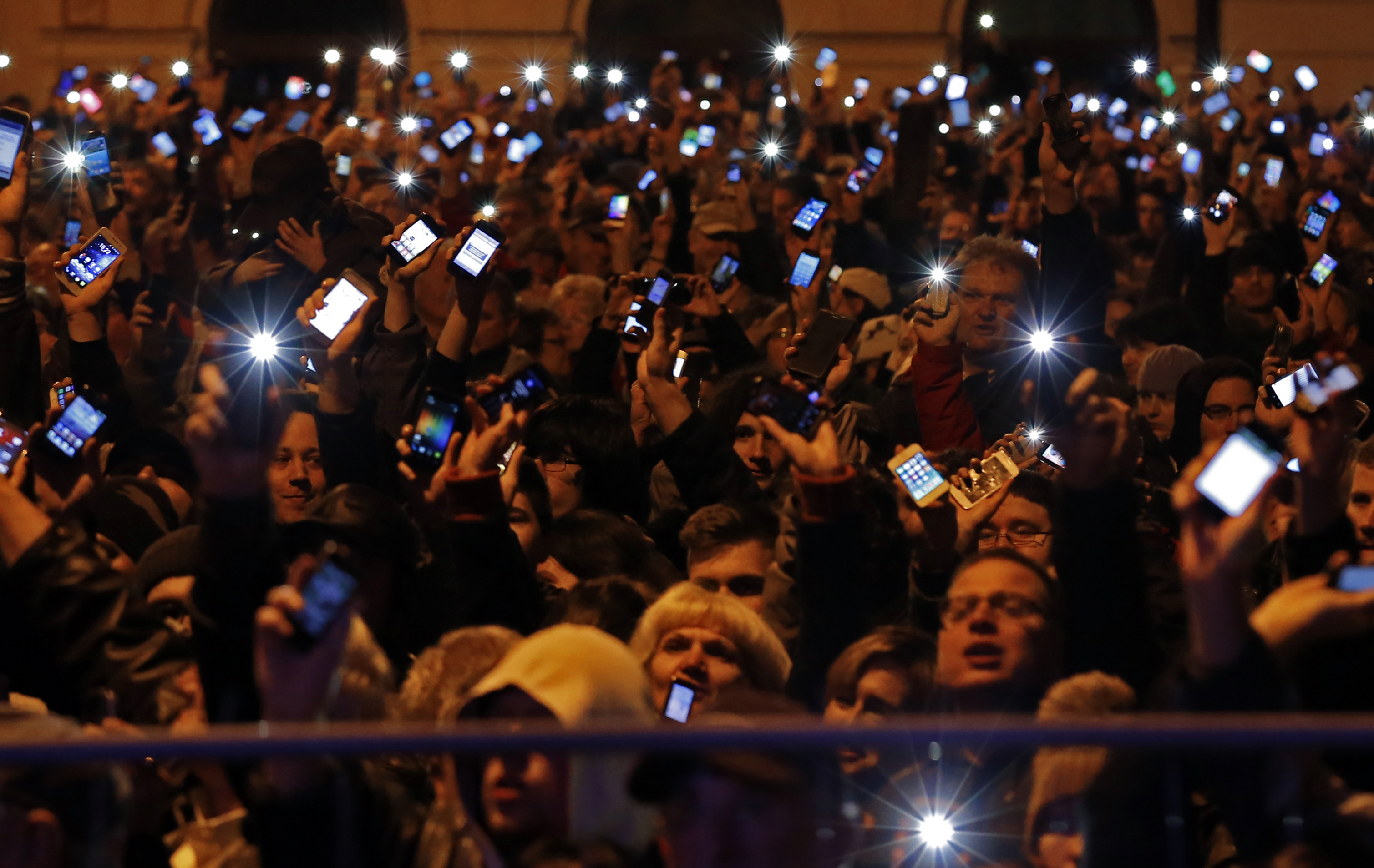 People hold up their mobile phones as they protest against a new tax on Internet data transfers in the centre of Budapest October 26, 2014 [Reuters]