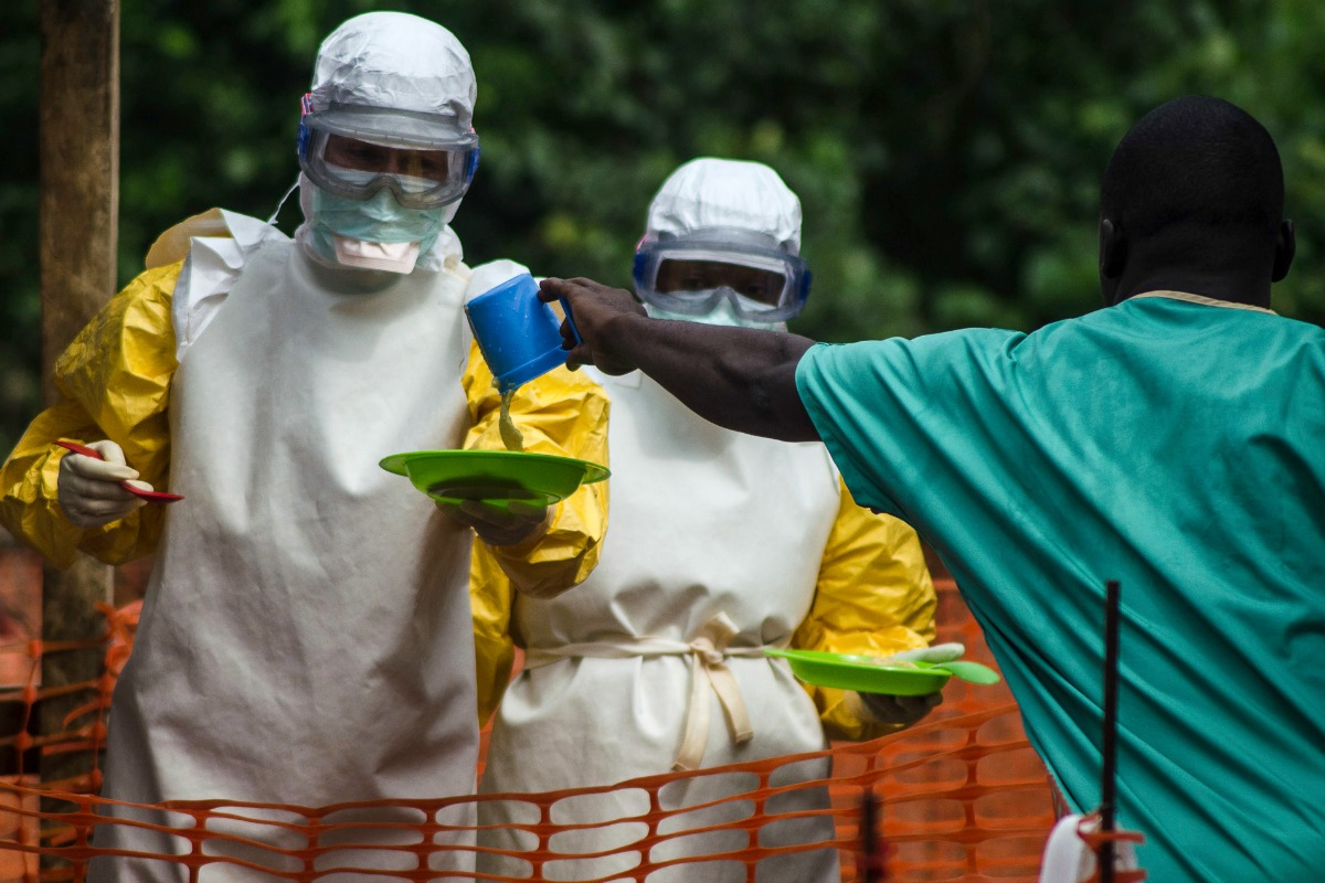 Le personnel médical avec Médecins sans Frontières (MSF) prepare to bring food to patients kept in an isolation area at the MSF Ebola treatment centre in Kailahun July 20, 2014 [Photo: Reuters]