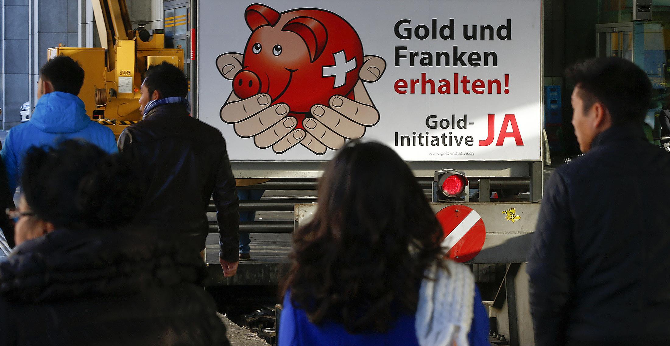 """Passants devant une affiche de la campagner """"Sauvez l'or de la Suisse"""" dans la gare principale à Zurich. [Reuters]"""